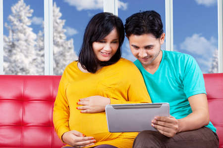 indian couple: Portrait of young man sitting on sofa with her pregnant wife while using a digital tablet