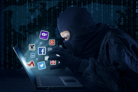 account data: JAKARTA, SEPTEMBER 21, 2015: Male thief wearing mask and stealing information of social media account like facebook, twitter, instagram, email, and yahoo with laptop