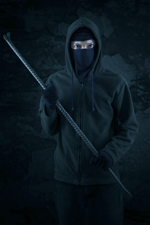 law breaker: Burglar with a crowbar is slink at night