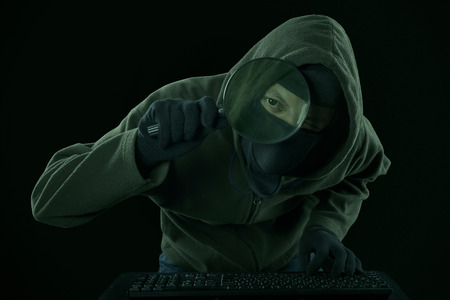 scammer: Internet Theft - a man wearing a balaclava looking at computer screen using magnifying glass