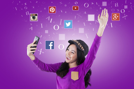 flickr: JAKARTA, SEPTEMBER 21, 2015: Image of happy teenage girl holding smartphone with social network icons like, facebook, twitter, instagram, path, etc Stock Photo