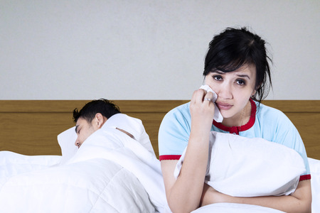 asian wife: Sad woman sitting on a bed while her husband is sleeping Stock Photo