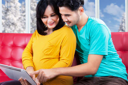indonesian woman: Portrait of young husband sitting on sofa with his pregnant wife while using a digital tablet Stock Photo