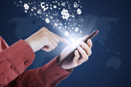 bank transfer: Photo of worker hand touching the mobile phone screen with currency symbols Stock Photo