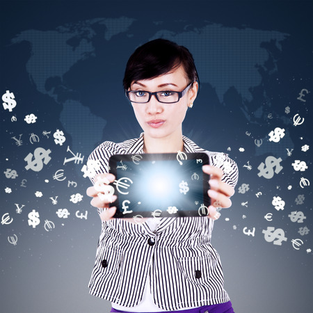 mobile technology: Image of young asian woman showing digital tablet screen with currency symbols flying away. Making money online concept Stock Photo