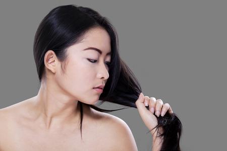 black hair: Encantadora mujer joven con la piel perfecta mirando su pelo negro sobre fondo gris