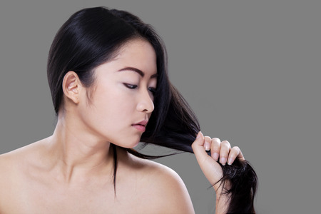 women hair: Lovely young woman with perfect skin looking at her black hair against grey background