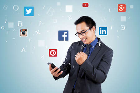 JAKARTA, SEPTEMBER 21, 2015: Photo of young asian businessman holding smartphone with social networks logo
