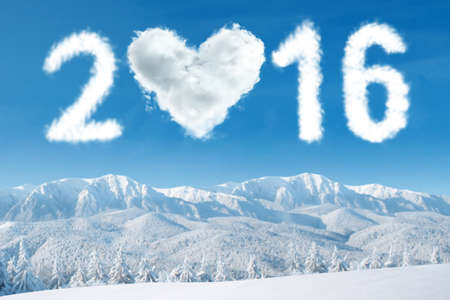 clear day in winter time: Image of cloud shaped numbers 2016 and heart symbol on the sky above snowy mountain. New year concept Stock Photo