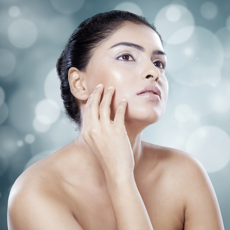 model face: Young indian woman touching her skin after spa treatment, shot in studio against bokeh background