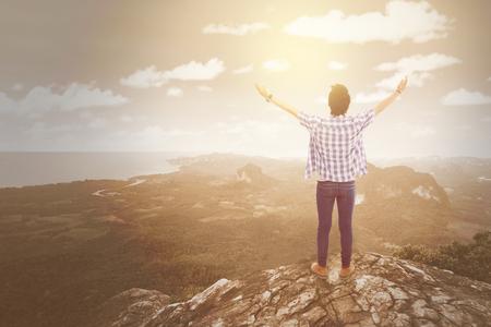 若い男は、山の崖の端に立っている、新鮮な空気をお楽しみください。Instagram のフィルターで撮影します。