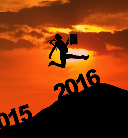 celebrate year: Silhouette of businesswoman jumping over 2016 numbers while carrying bag to celebrate new year Stock Photo
