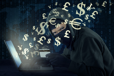 Image of male hacker wearing mask and using laptop while holding credit card to steal money through online transaction