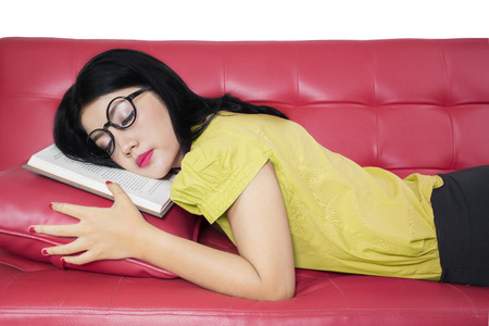 red sofa: Image of beautiful female student napping on the sofa after reading a book Stock Photo