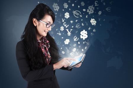 Foto van jonge vrouwelijke werknemer met behulp van digitale tablet met valuta symbolen wegvliegen. Het maken van geld online concept