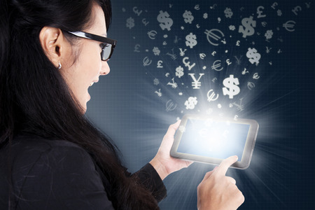 money online: Young businesswoman touching a digital tablet screen with currency symbols. Making money online concept
