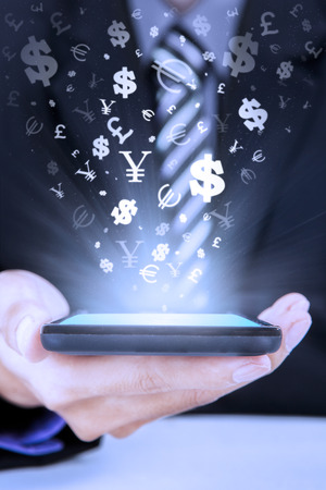 currencies: Photo of entrepreneur hand holding mobile phone with currency symbols coming out from the screen Stock Photo