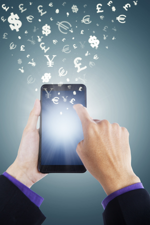 flying money: Image of hands holding smartphone with currency symbols flying away. Making money concept
