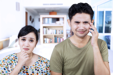 persons: Sad couple expression at home with bookshelf