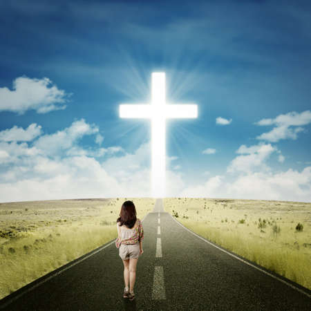 beautiful jesus: Back view of young girl walking alone on the road toward a cross on the end of the road Stock Photo