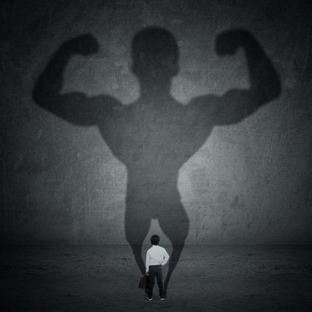 fortaleza: Pequeño hombre de negocios que echa una sombra de un atleta - concepto de negocio y la fuerza de carrera