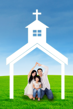 green cross: Happy family sitting under church symbol Stock Photo