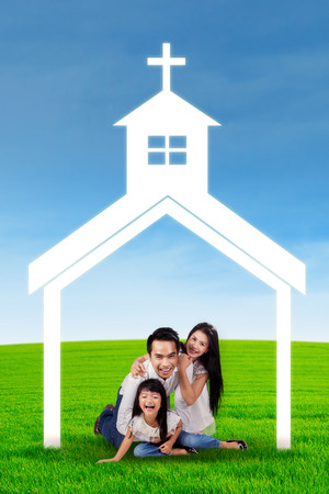 happy asian family: Portrait of happy family playing together on the meadow under church symbol Stock Photo