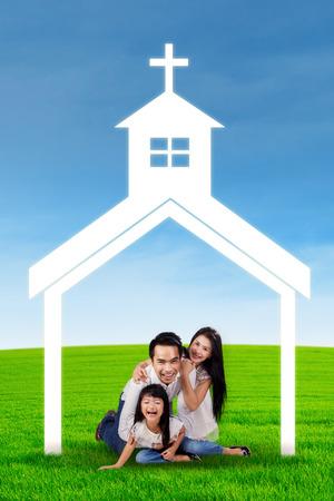 familia cristiana: Retrato de familia feliz jugando juntos en la pradera bajo el símbolo de la iglesia Foto de archivo