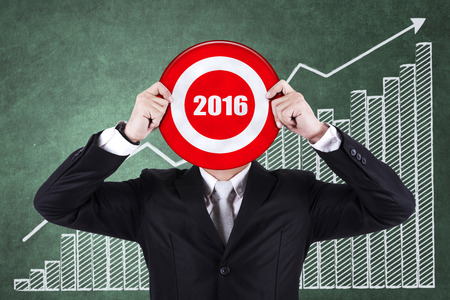 financial targets: Image of businessman holding a dartboard with numbers 2016 in front of financial chart