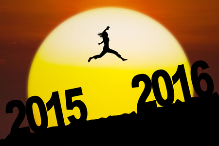 new years resolution: Silhouette woman jumping above numbers 2016 on the hill at sunset time. New year concept Stock Photo