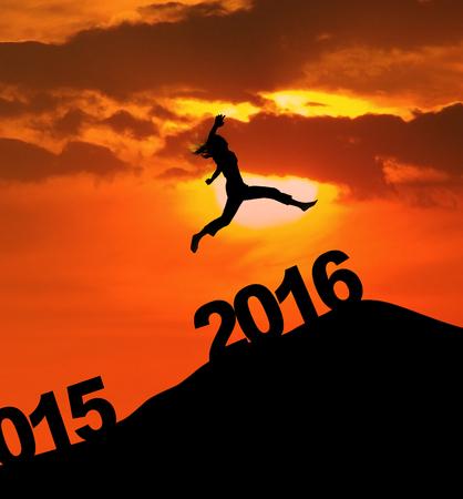 nowy rok: Zdjęcie z sylwetka kobiety skacze na wzgórzu nad numerami 2016 w czasie zmierzchu. koncepcji nowy rok Zdjęcie Seryjne