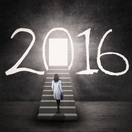 escalera: Imagen de la empresaria caminando por las escaleras mientras llevar malet�n hacia una entrada con los n�meros 2016