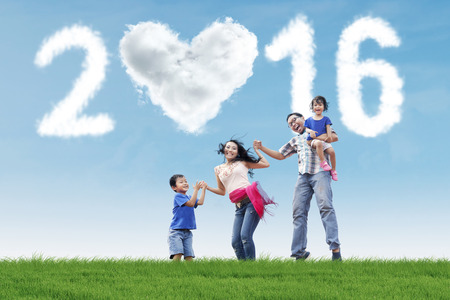 celebrate year: Portrait of cheerful family celebrate new year on the meadow and jumping together with cloud shaped numbers 2016 Stock Photo