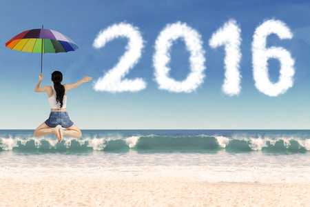 Image of happy woman jumping on the beach while holding umbrella with cloud shaped numbers 2016