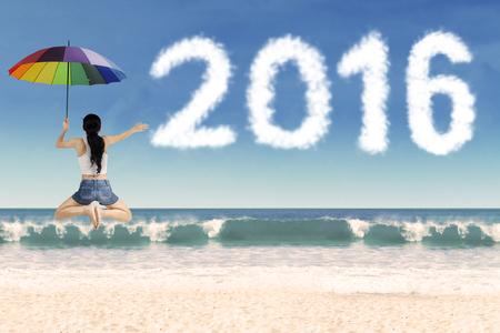 persona alegre: Imagen de la mujer feliz saltando en la playa mientras que sostiene el paraguas con los n�meros en forma de nube de 2016 Foto de archivo
