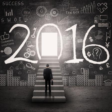 Zakenman met formele kleding lopen op de trap naar de deur met cijfers 2016 en krabbels op de muur Stockfoto