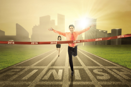 rival: Image of young businessman defeat his rival in a race competition and crossing the finish line with numbers 2016