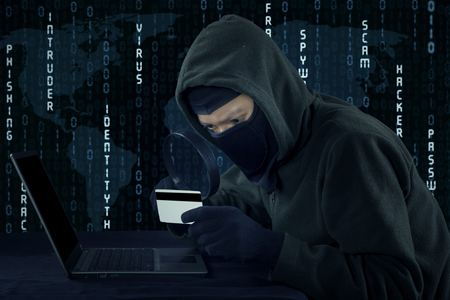 web scam: Image of male villain wearing mask and using laptop computer while holding credit card Stock Photo