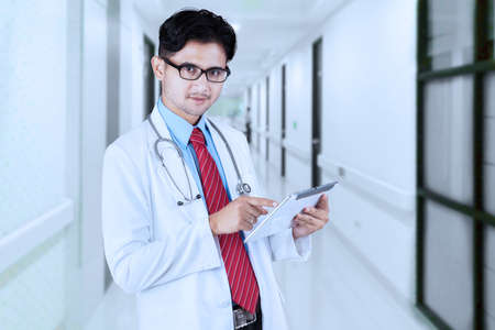 physicians: Portrait of young doctor standing in the hospital alley while using a digital tablet