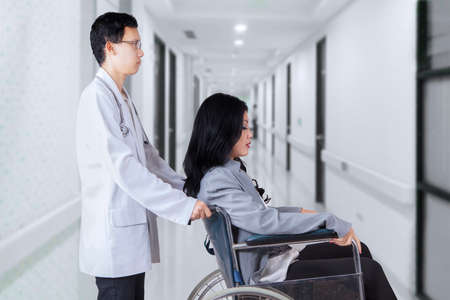 patient in hospital: Image of male doctor pushing female patient with wheelchair in the hospital corridor Stock Photo