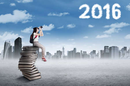 education goals: Image of female high school student sitting on the stack of books while using binoculars to see cloud shaped numbers 2016 Stock Photo