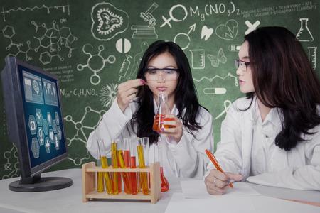 experimento: Retrato de dos bastante científico que trabaja juntos y hacer la investigación con el líquido químico en el laboratorio Foto de archivo