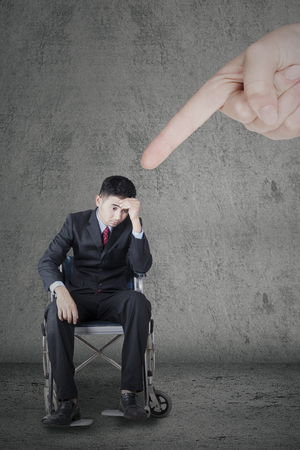 work stress: Image of disabled businessman sitting on the wheelchair and looks frustrated with a finger pointing him