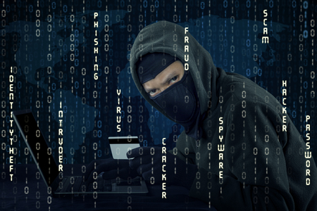 web scam: Male hacker holding credit card while using laptop computer and wearing mask Stock Photo