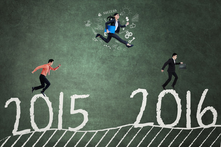 compete: Group of young businesspeople jumping above numbers 2015 to 2016 and compete to each other