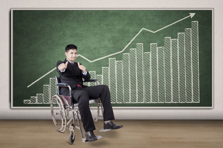 sit up: Portrait of disabled businessman showing hands gesture in front of financial chart