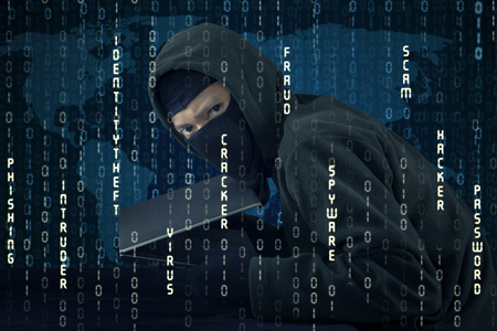 identities: Image of male hacker wearing mask and holding laptop computer with binary code background. Identity theft concept