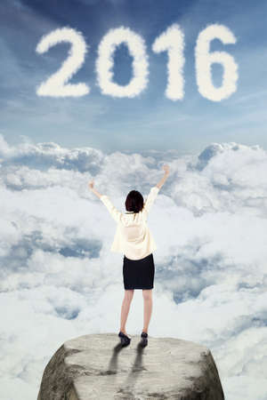 dream vision: Photo of young businesswoman standing on the cliff while raising hands and looking at cloud shaped numbers 2016 Stock Photo
