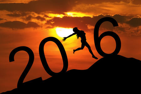 success symbol: Silhouette young woman jumping on the hill and forming numbers 2016 while celebrating new year