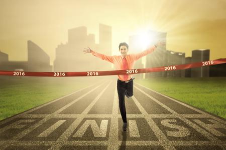 Homme d'affaires prospère remportant la compétition de course et franchir la ligne d'arrivée avec des numéros 2016 Banque d'images